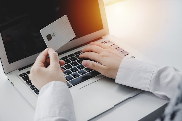 모바일뱅킹. 홈 오피스, 인터넷, 디지털 마케팅, 온라인 쇼핑, 온라인 지불 및 디지털 기술 개념의 책상 위에 있는 노트북 컴퓨터에서 신용 카드와 온라인 쇼핑을 들고 있는 손