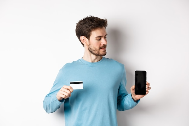 Mobile banking. handsome caucasian man showing plastic credit card and looking at blank mobile screen, standing over white background.