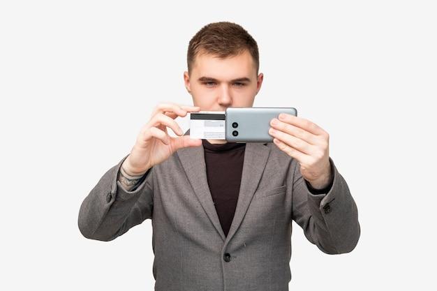 모바일뱅킹. 온라인 결제. 신용 카드 스마트폰 흰색 절연을 사용 하 여 자신감이 사업가.