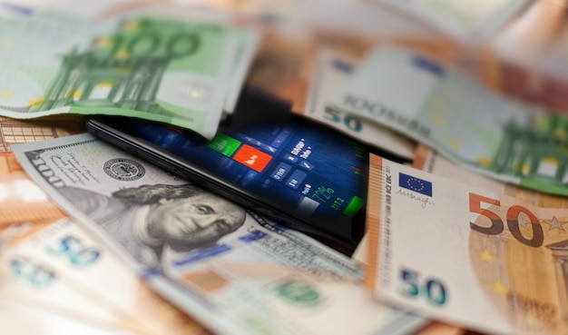 Mobile banking smartphone with stock exchange market application euro and us dollar banknotes