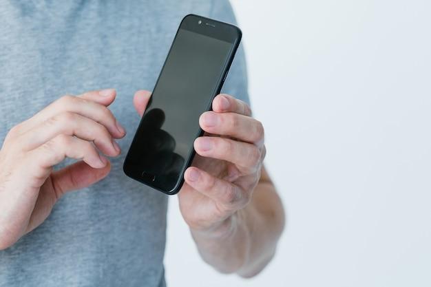 모바일 비즈니스 및 전자 상거래. 온라인 디지털 마케팅. 인터넷에서 돈을 벌 수 있습니다. 빈 검은 화면으로 스마트 폰을 들고 남자.