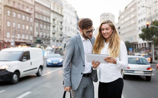 Мобильные деловые люди гуляют, разговаривают в центре города