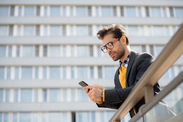 도시 환경에서 난간에 기대어 자신의 스마트 폰에서 안경 및 스마트 캐주얼 독서 알림의 모바일 사업가