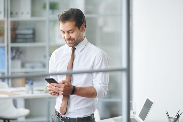 モバイルビジネスマンがオフィスでの勤務中にスマートフォンの連絡先をスクロール