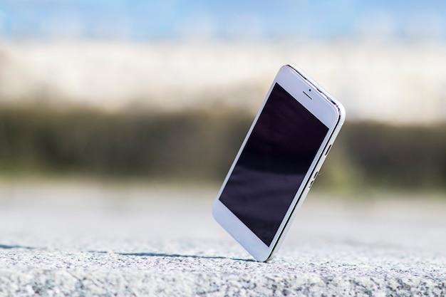 モバイルセルスマートフォンが手から落ち、アスファルトの上でクラッシュします。壊れたスマートフォンが床に落ち、ガジェット、デバイスを修理する必要があります。電話での事故。ひび割れたディスプレイ。サービスコンセプト