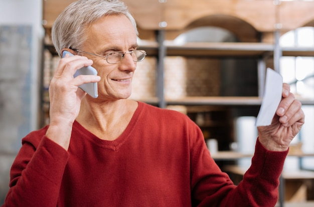 モバイル通信。陽気な素敵な老人が彼の耳に電話を置き、彼の対話者と話している間笑顔