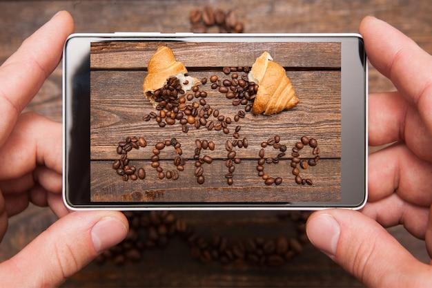 モバイルコンセプチュアル写真。ソーシャルネットワーク、上面図の木製の背景にコーヒー豆と甘いデザートによって作られた碑文の写真を撮る手で電話