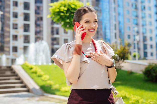 モバイル接続。電話で話しながら彼女の耳に電話を置く快適な幸せな女