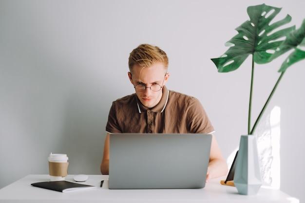 Mobile developer programmer writes program code on a laptop computer in home office