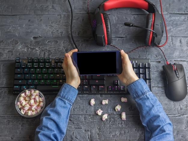컴퓨터 시설을 갖춘 책상의 배경에 어린이의 손에 모바일 장치
