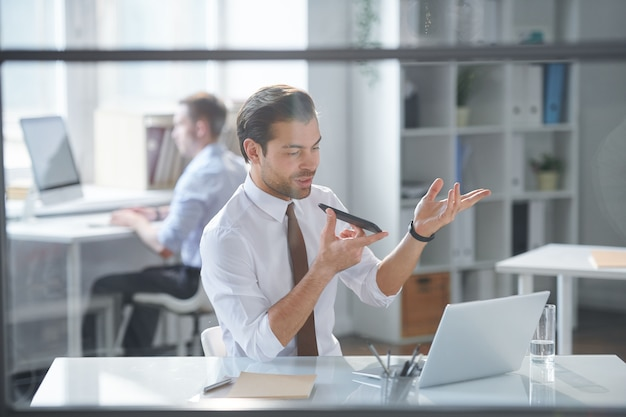 Mobile elegant businessman sitting in office while recording voice message on smartphone by workplace