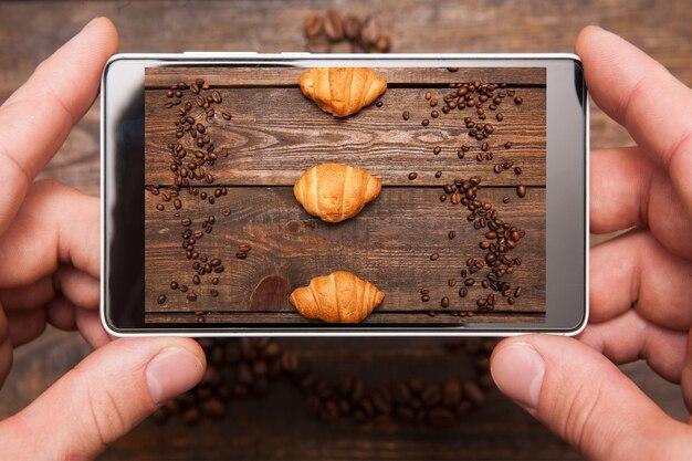 モバイルフードフォトグラフィー。手に携帯電話は、木製の背景、上面図でコーヒー豆とデザートを撮影しています