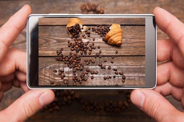 モバイルフードフォトグラフィー。ソーシャルネットワーク、上面図の木製の背景にコーヒー豆と甘いデザートの写真を撮る手で電話