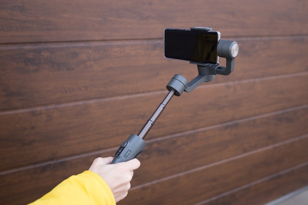 Mobile image stabilizer for smartphones on a white isolated wall.