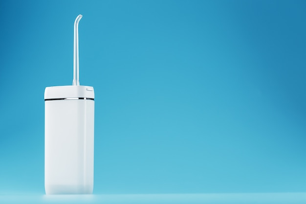 Mobile irrigator for cleaning the oral cavity on a blue surface