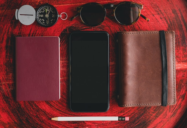 Mobile and notebook and passport on red table for travel