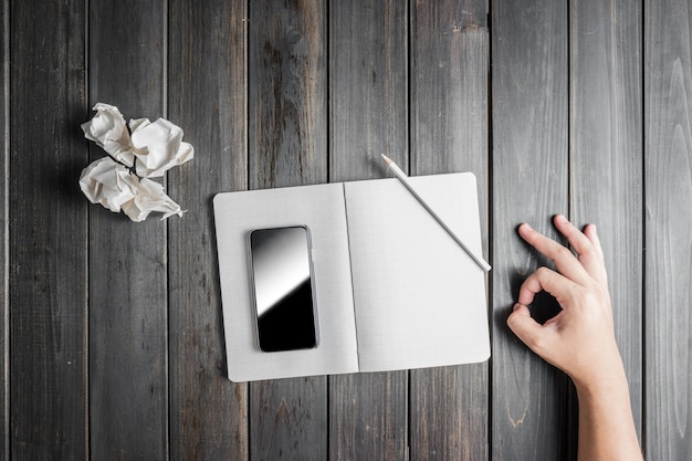 Mobile on notebook with hand showing a positive gesture