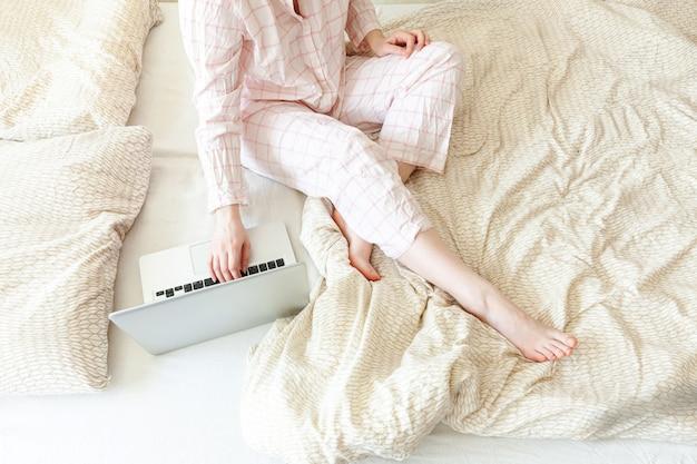 집에서 모바일 오피스. 잠 옷에 젊은 여자 집에서 침대에 앉아 노트북 pc 컴퓨터를 사용 하여 작업. 실내 공부하는 라이프 스타일 소녀. 프리랜서 사업 격리 개념입니다.