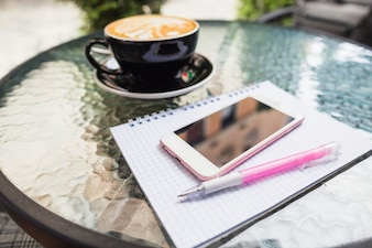 Mobile on checked notebook and pen with coffee on an outdoors table