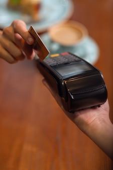 모바일 결제. 은행 단말기는 여성의 손과 여성의 손으로 신용 카드 또는 직불 카드로 결제를합니다.