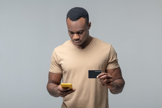 Mobile payment. serious attentive black man with credit card looking into smartphone making payment transaction