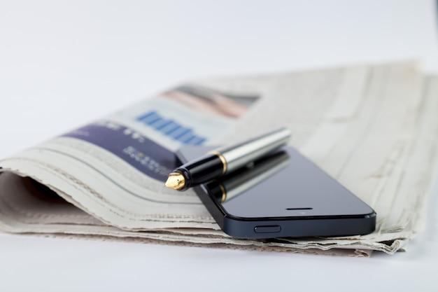 テーブルの上の携帯電話、ペン、新聞