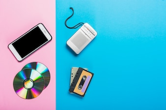 Mobile phone and cd replaced with tape recorder and cassette on dual pink and blue backdrop