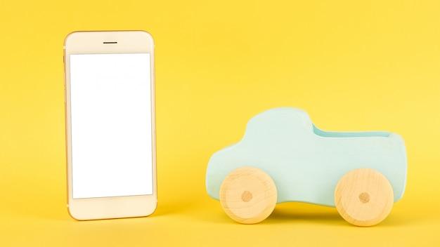 Мобильный телефон и детская голубая игрушечная машинка