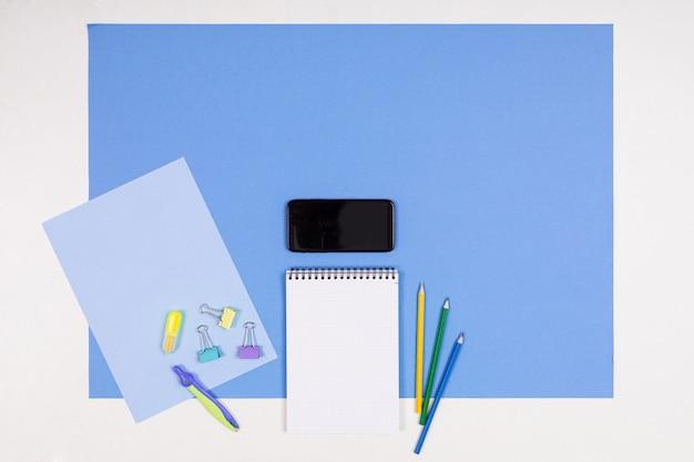 Мобильный телефон и различные канцелярские принадлежности, изолированные на белом и синем