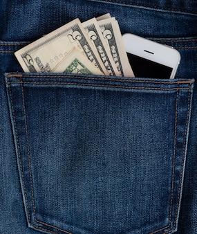 청바지 주머니에 휴대 전화 및 달러 지폐