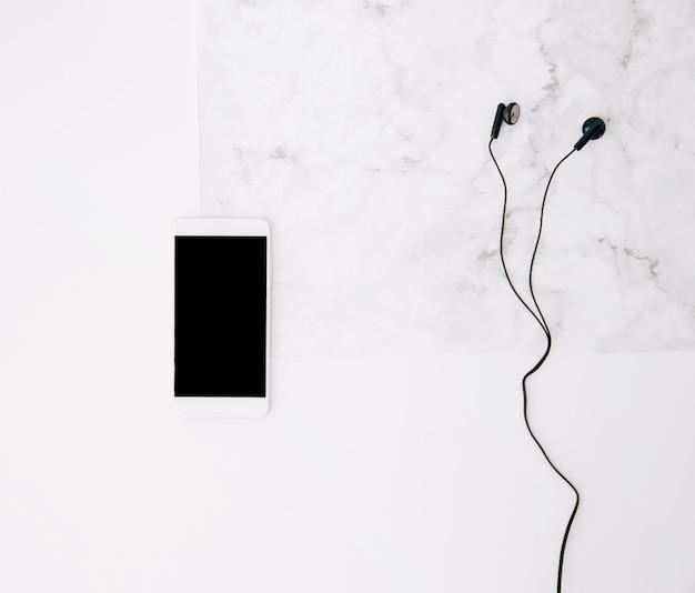 携帯電話と白い織り目加工の背景にイヤホン