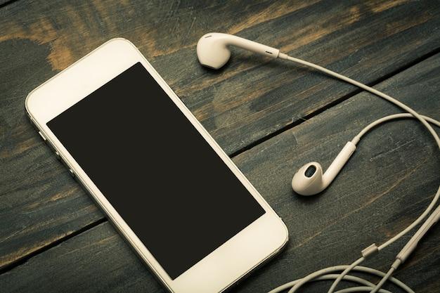 나무 배경에 휴대 전화와 이어폰