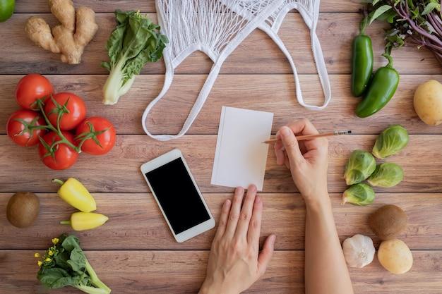 ネットエコバッグと木製のテーブルに新鮮な野菜の携帯電話とメモのリスト。オンライン食料品および有機農家製品ショッピングアプリケーション。食品および調理レシピまたは栄養カウント。