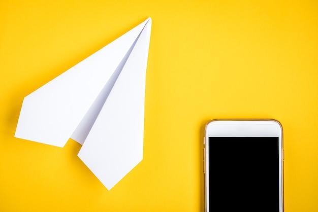 Мобильный телефон и бумажный самолетик на желтом