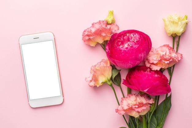 携帯電話とパステル調の背景にピンクの花の花束