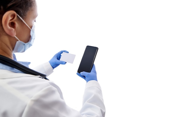 白い背景で隔離の医師の手に携帯電話とプラスチックカード。健康保険の概念