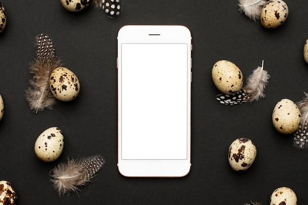 黒の背景上の羽を持つ携帯電話とウズラの卵。ホリデーイースター、ミニマルな黒の構図