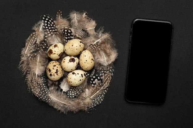 携帯電話とウズラの卵、黒い背景に羽