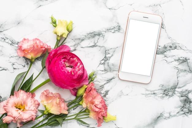 携帯電話と大理石の背景にラナンキュリピンクの花の花束