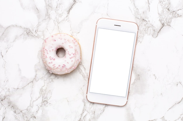 大理石の背景に携帯電話と甘いドーナツ