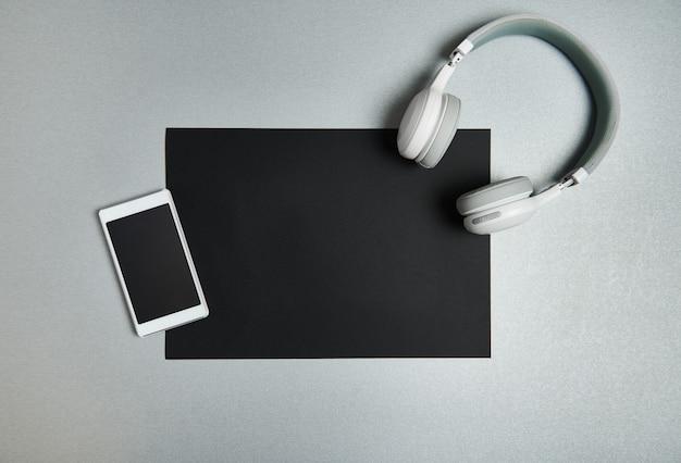 휴대 전화 및 회색 배경에 종이의 검은 시트에 무선 헤드폰. 흑인과 백인 정물. 평평하다. 평면도.