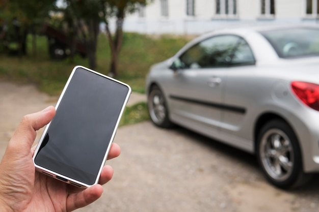 자동차 소유자 개념을 위한 휴대 전화 앱. 스마트 폰을 사용하여 상태를 확인하고 새 차를 제어하는 남자. 디자인을 위한 빈 빈 휴대 전화 화면입니다.