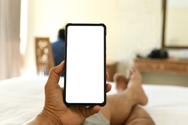 손에 휴대 전화 빈 화면. 그는 방에 침대에서 잤다.