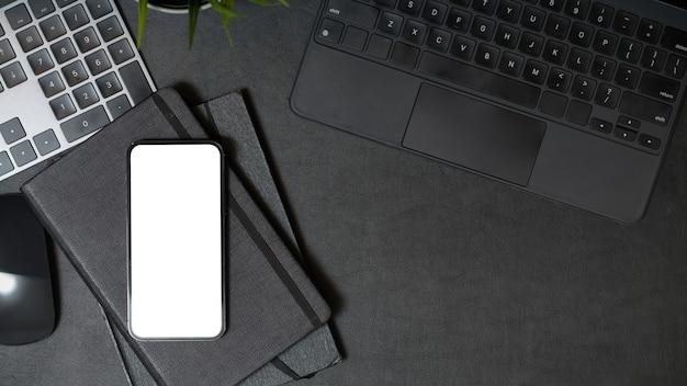黒い作業台にコピースペースキーボードとノートブックを備えた携帯電話の空白の画面のモックアップ上面図