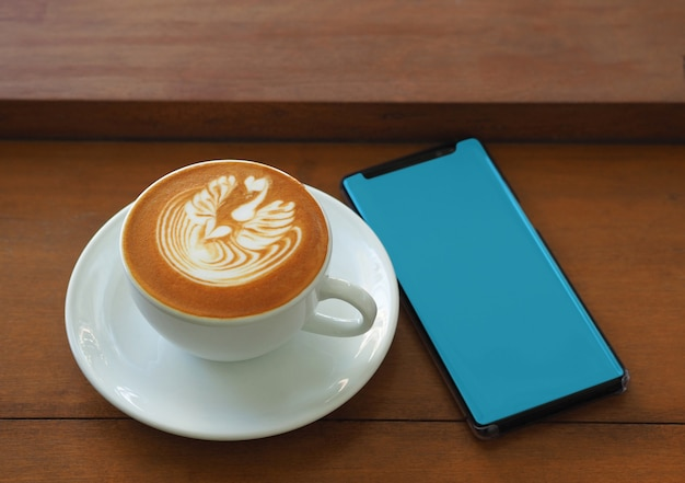 Mobile phone blank screen with cappuccino coffee on wooden table in coffee shop