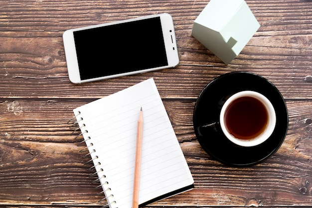 Mobile phone; blank spiral notebook; pencil; coffee cup and house model on wooden desk