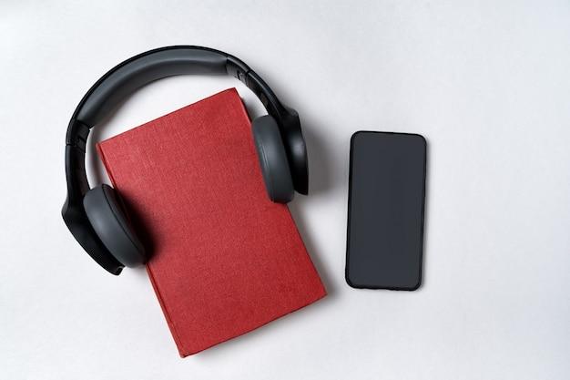 携帯電話、本、白い背景の上のヘッドフォン。オーディオブックのコンセプトです。トップビュー、コピースペース。