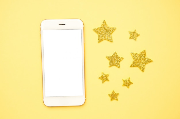 Mobile phone and brilliant glitter stars on a yellow , technology and rating