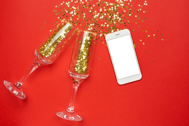 Mobile phone and champagne glasses with golden stars confetti, christmas and new year concept