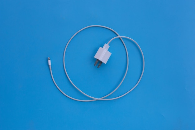 Mobile phone charger on blue wall.
